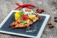Grilled tiger prawns with grilled vegetables on a square plate Stock Image
