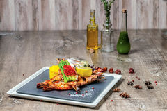 Grilled tiger prawns with grilled vegetables on a square plate Royalty Free Stock Image