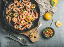 Grilled tiger prawns in pan with lemon, leek, chili, sauce royalty free stock images