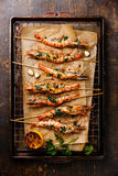 Grilled Tiger shrimps on skewers with green sauce Royalty Free Stock Photo