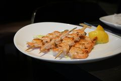 Grilled tiger shrimps skewers with lemon stock photo
