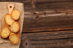 Grilled toasts on old wooden background and space for text Royalty Free Stock Photography