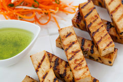Grilled tofu. Grilled japanese style tofu slices with dipping sauce Royalty Free Stock Photography
