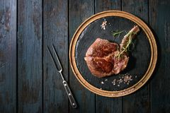Grilled tomahawk steak. Grilled black angus beef tomahawk steak on bone served with salt, pepper and rosemary on round wooden slate cutting board with meat fork royalty free stock image