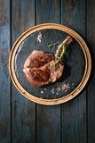 Grilled tomahawk steak. Grilled black angus beef tomahawk steak on bone served with salt, pepper and rosemary on round wooden slate cutting board over dark royalty free stock image