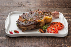 Grilled tomahawk steak on the bone on a ceramic plate. Horizontal royalty free stock images