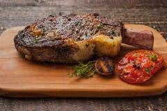 Grilled tomahawk steak on the bone on a cutting board