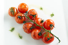 Grilled tomatoes cherry decorated green leaves. White plate Stock Photo