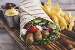 Grilled tortilla wrap sausages fresh vegetables and sauce. A stock photography