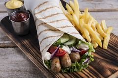 Grilled tortilla wrap sausages fresh vegetables and sauce. A stock image