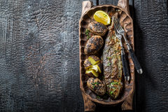 Grilled trout fish and potatoes with herbs and butter Royalty Free Stock Photography
