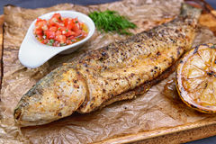 Grilled trout on paper, with sauce and lemon stock photo
