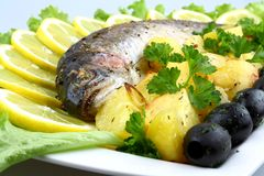 Grilled trout with potato, salad, black olives, lemon Royalty Free Stock Image