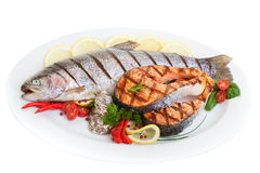 Grilled Trout. And salmon steak with vegetables and oysters Stock Photos