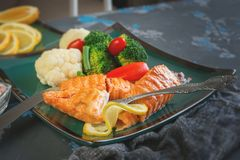 Grilled trout with steamed vegetables and lime. Close up. stock photography