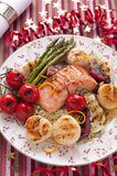 Grilled trout with vegetables and scallops. Grilled trout with vegetables, scallops and couscous garnished with orange rind royalty free stock image
