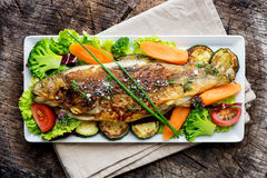 Grilled trout with vegetables. On wooden background Royalty Free Stock Photo