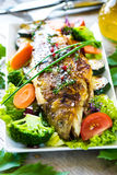 Grilled trout with vegetables. On wooden background Stock Photos