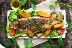Grilled trout with vegetables. On wooden background Stock Photography