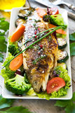 Grilled trout with vegetables. On wooden background Royalty Free Stock Image