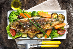 Grilled trout with vegetables. On wooden background Royalty Free Stock Photography