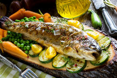 Grilled  trout  with  vegetables. On wooden background Stock Photo