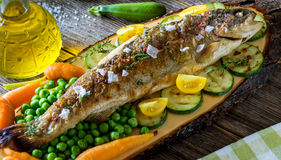 Grilled  trout  with  vegetables. On wooden background Royalty Free Stock Photos