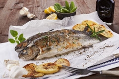Grilled trouts. Two grilled trouts on white plate with lemon pieces, potatoes and balsamico on kitchen towel on wooden table Stock Photo