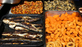 Grilled trouts, calamar rings and shells Stock Photography