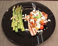 Grilled Tuna and Asparagus Dinner. Grilled Tuna Steak with Feta, Tomato Salsa with a side of grilled Asparagus Stock Photos