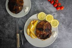 Grilled Tuna With Garlic, Lemon, Cherry Tomatoes, Potato Chips and Tartar Sauce stock photo