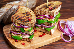 Grilled Tuna Sandwich with onion, olives and pomegranate seeds royalty free stock image