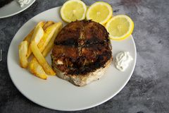 Grilled tuna seasoned with lemon, garlic and potatoes. Healthy food royalty free stock image