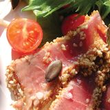 Grilled tuna with sesame and side salad. Served in Italy Royalty Free Stock Photo