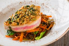 Grilled tuna steak with garnish from salad, carrots and mushroom Royalty Free Stock Photo