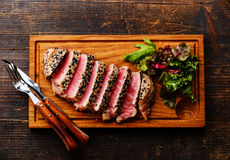 Grilled Tuna steak and Green salad. Grilled Tuna steak in sesame and Green salad on wooden board on dark wooden background Royalty Free Stock Photos