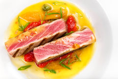 Grilled tuna steak with sauce, herbs and cherry tomatoes in a wh Royalty Free Stock Photography