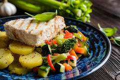 Grilled tuna with steamed vegetable salad. Grilled tuna steaks with steamed broccoli, red pepper, zucchini, parsley, stalk celery and carrot Royalty Free Stock Photography
