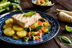 Grilled tuna with steamed vegetable salad. Grilled tuna steaks with steamed broccoli, red pepper, zucchini, parsley, stalk celery and carrot Royalty Free Stock Photos
