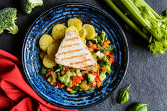 Grilled tuna with steamed vegetable salad. Grilled tuna steaks with steamed broccoli, red pepper, zucchini, parsley, stalk celery and carrot Stock Photos