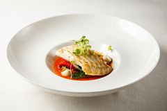 Grilled turbot, tabouli, sweet pepper sauce and summer vegetables. White dish Stock Photo
