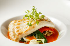Grilled turbot, tabouli, sweet pepper sauce and summer vegetables. White dish Royalty Free Stock Images
