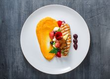 Grilled turkey fillet with pumpkin puree and vegetables on white plate. Close view. stock photos