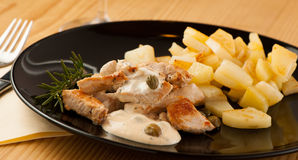 Grilled turkey meat with cheese sauce and capers on black plate Stock Image