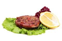 Grilled turkey steak with lemon and pomegranate on leaf of salad Stock Images