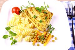 Grilled turkey steak with noodles peas, carrots, tomato and oregano Royalty Free Stock Photo
