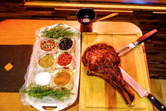 Grilled veal chop on wooden table with spices and herbs. royalty free stock photography