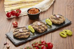 Grilled Veal minced meat with spices on black stone and wooden background stock images