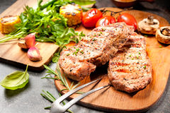 Grilled veal steaks on cutting board Royalty Free Stock Images