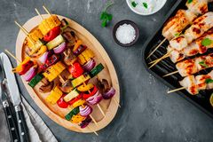 Grilled vegetable and chicken skewers with sweet corn, paprika, zucchini, onion, tomato and mushroom. On a wooden plate, top view royalty free stock photo